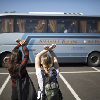 Activists gesture towards a bus carrying African migrants in Tel Aviv as it leaves enroute Israel's new detention centre