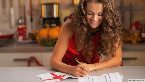 Happy young housewife signing christmas postcards in kitchen; Shutterstock ID 158618495; PO: TODAY.com